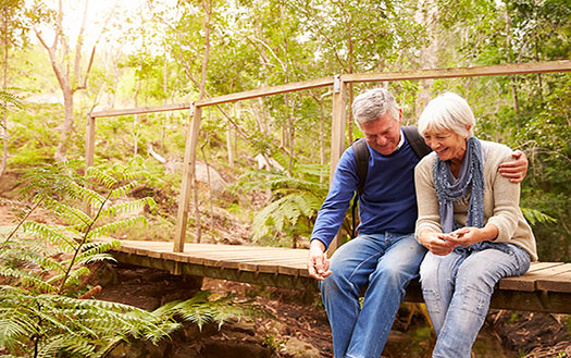 mature couple sitting on a samll wooden bridge