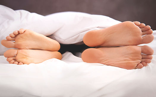 couple in bed feet facing away form each other